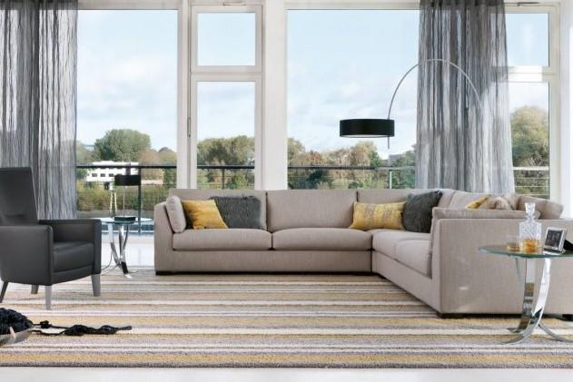 eingerichtetes Wohnzimmer mit grauem Ecksofa, Tischelementen und einem schwarzen Sessel von den Bielefelder Werkstätten