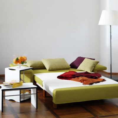 Signet Schlafsofa PAULA mit grünem Stoff in Schlafposition vor weißem Kamin Liegefläche 133 x 209 cm
