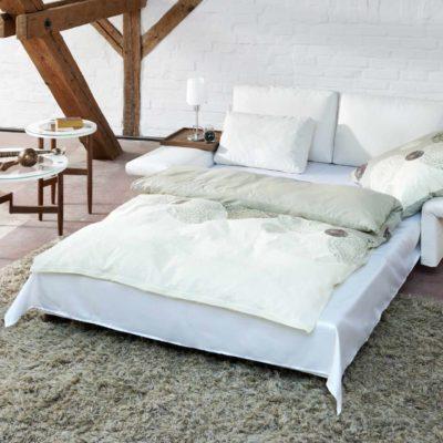 Signet Schlafsofa PAULA mit weißem Stoff in Schlafposition vor weißer Steinwand Liegefläche 133 x 209 cm